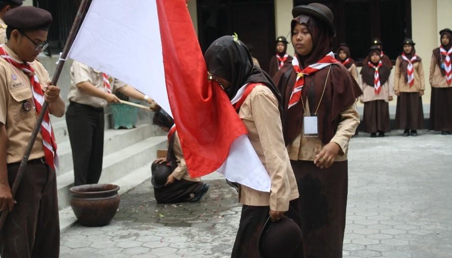 Peserta mencium bendera merah putih saat upacara pelantikan tamu racana